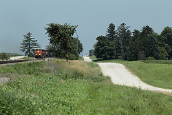 A Burlington Northern Santa Fe Freight Train emerges from a small wooded area between a paved road and a gravel road just south of Wataga Illinois.