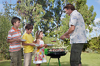 Father serving grilled food to children (5-11) in line