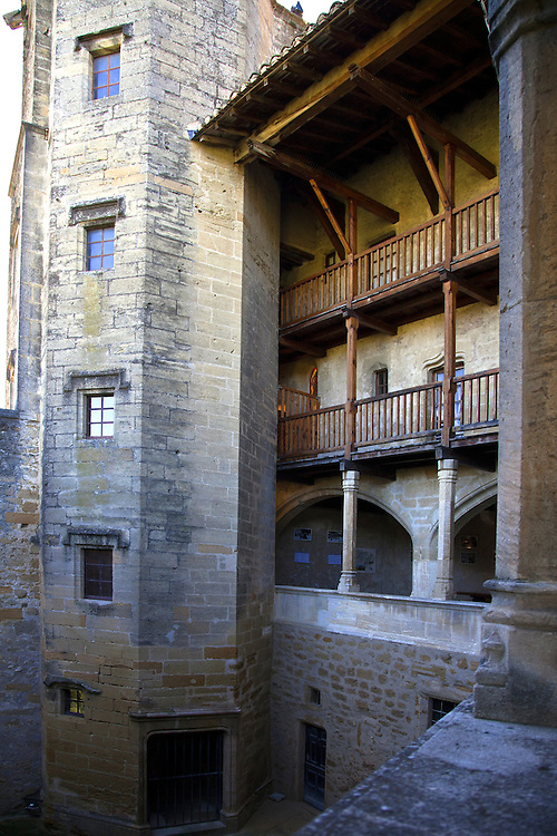Behind massive walls, the exterior of the medieval wing of the Chateau de Lourmarin gives access to a series of small stone-lined rooms.