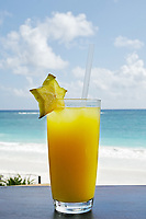 a glass of fruit orange juice with blue sky and sea in the background