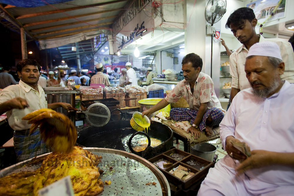 "Abdul Muttalib (R) overlooks as ""Malpua"" a sweet pancake dish is made at a stall, opposite Minara masjid at Mohammed Ali road in Mumbai, Maharashtra, India, on Saturday September 6, 2009. Photographer: Prashanth Vishwanathan/The National"