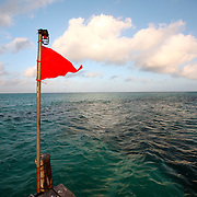 A red flag waves in front of the ocean off a pier on Isla Mujeres, near Cancun, Mexico. The island is world-renowned for its beautiful beaches, resorts, sport fishing, and diving opportunities.