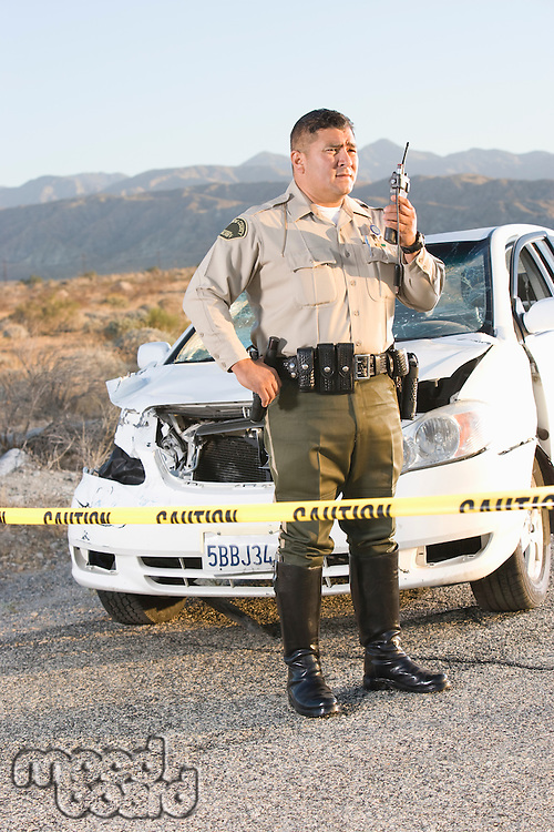 Police officer using radio in front of damaged car in desert