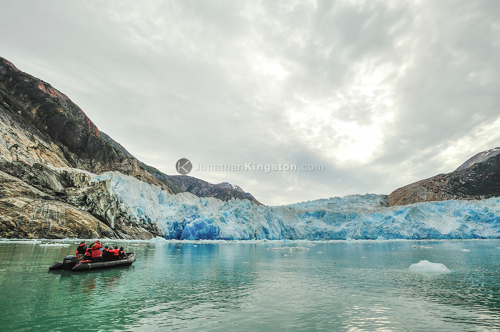 Small inflatable boat with tourists plies the waters in front of the Dawes glacier in Tracy arm fjord near Juneau, Alaska.