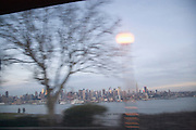 blurry view of tree and street light with midtown Manhattan in the back ground New Jersey side