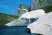 """Dragon Lake, snow banks, Gamila Peak, Vikos-Aoos National Park, north Pindus Mountains (Pindos or Pindhos), Zagoria, Epirus/Epiros, Greece, Europe. The northeast wall of Vikos Gorge is Mount Tymfi (or Greek: , also transliterated Mt Timfi, Tymphe, or Tymphi), near the 40 degree parallel. Tymfi forms a massif with its highest peak, Gamila, at 2497 meters (8192 feet), the sixth highest in Greece. Zagori (Greek: ) is a region and a municipality in the Pindus mountains in Epirus, in northwestern Greece. Zagori contains 45 villages collectively known as Zagoria (Zagorochoria or Zagorohoria). Published in """"Pindos: The National Park"""" (2010) by Alexander G. Tziolas, preface by Tom Dempsey et al, ISBN 978-960-98795-3-8."""