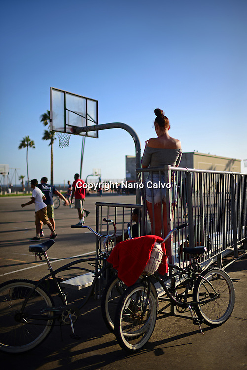 Young woman using smartphone and people playing street basketball game, Venice Beach.
