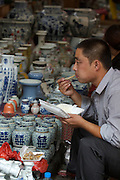 Panjiayuan weekend market. Porcelaine and ceramics shop owner having fast food lunch.