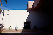 A woman sits alone outside of the Sundial Auditorium in Sun City, Arizona December 9, 2009.