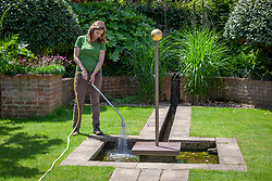 Topping up a water feature in summer using a hosepipe