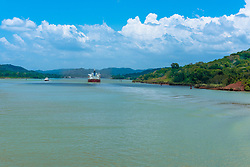 A large tanker and smaller boat sail along Gatun Lake in the Panama Canal Complex