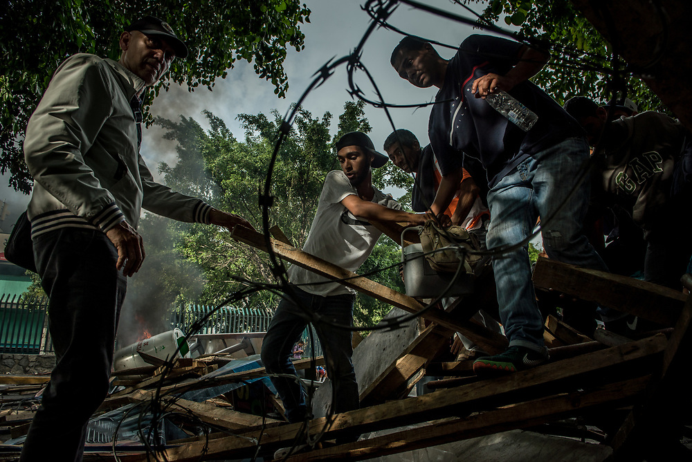 CARACAS, VENEZUELA - MAY 24, 2017:  People climb over a road block built by anti-government protesters to block police and soldiers from entering, during a street protest in Caracas.  The streets of Caracas and other cities across Venezuela have been filled with tens of thousands of demonstrators for nearly 100 days of massive protests, held since April 1st. Protesters are enraged at the government for becoming an increasingly repressive, authoritarian regime that has delayed elections, used armed government loyalist to threaten dissidents, called for the Constitution to be re-written to favor them, jailed and tortured protesters and members of the political opposition, and whose corruption and failed economic policy has caused the current economic crisis that has led to widespread food and medicine shortages across the country.  Independent local media report nearly 100 people have been killed during protests and protest-related riots and looting.  The government currently only officially reports 75 deaths.  Over 2,000 people have been injured, and over 3,000 protesters have been detained by authorities.  PHOTO: Meridith Kohut