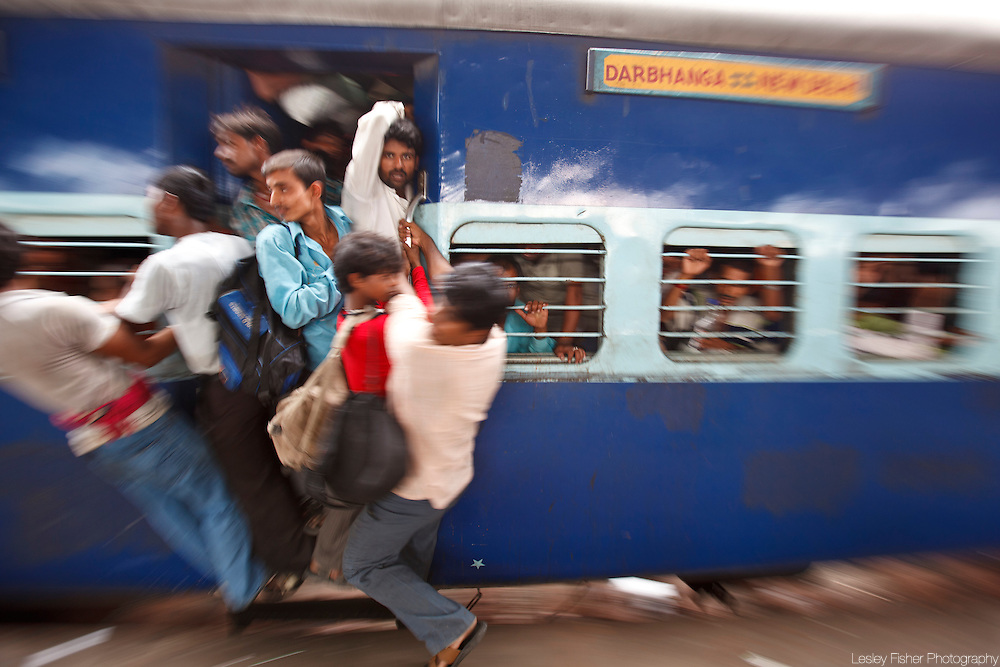 Passengers cramped and hanging on to a departing train at New Delhi Train Station, Delhi, India