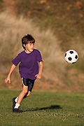 Boy playing with soccer ball in early evening sunlight
