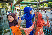 26 OCTOBER 2012 - PULASAIZ, NARATHIWAT, THAILAND: Girls play on the swings in the courtyard of the mosque on the holiday of Eid al-Adha in the villiage Pulasaiz, in the province of Narathiwat, Thailand. Eid al-Adha, also called Feast of the Sacrifice, is an important religious holiday celebrated by Muslims worldwide to honor the willingness of the prophet Ibrahim (Abraham) to sacrifice his firstborn son Ishmael as an act of submission to God, and his son's acceptance of the sacrifice before God intervened to provide Abraham with a ram to sacrifice instead. In 2012 Eid al-Adha was celebrated Oct 25 - 26.     PHOTO BY JACK KURTZ