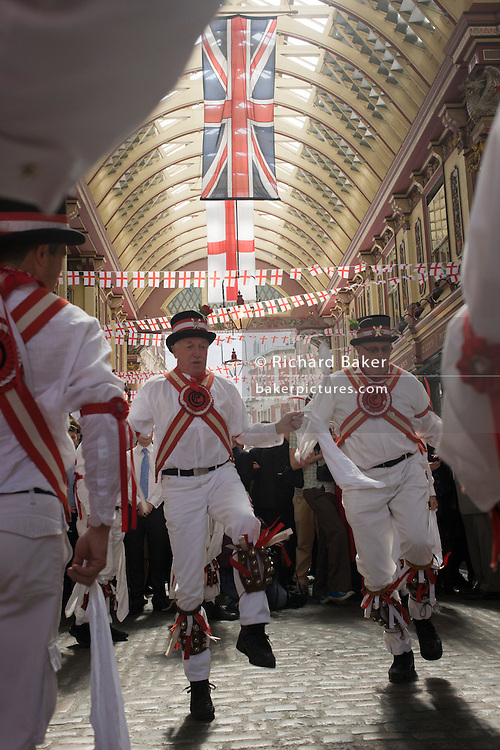 Morris man and lunchtime drinkers gather in Leadenhall Market on St George's Day, when 'Englishmen' celebrate their patron saint. Wearing white uniforms they jig their traditional dance, a form of English folk dance accompanied by accordion and pipes. It is based on rhythmic stepping and the execution of choreographed figures by a group of dancers. Implements such as sticks, swords, and handkerchiefs may also be wielded by the dancers. In a small number of dances for one or two men, steps are performed near and across a pair of clay tobacco pipes laid across each other on the floor. English records of Morris dancing date back to 1448.
