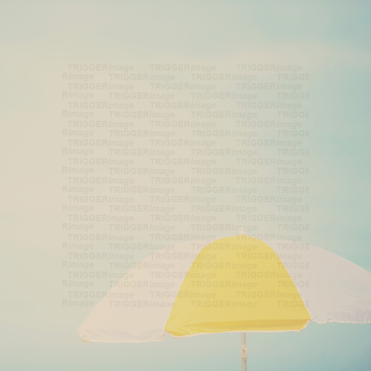 a yellow and white beach umbrella on a beautiful summer afternoon