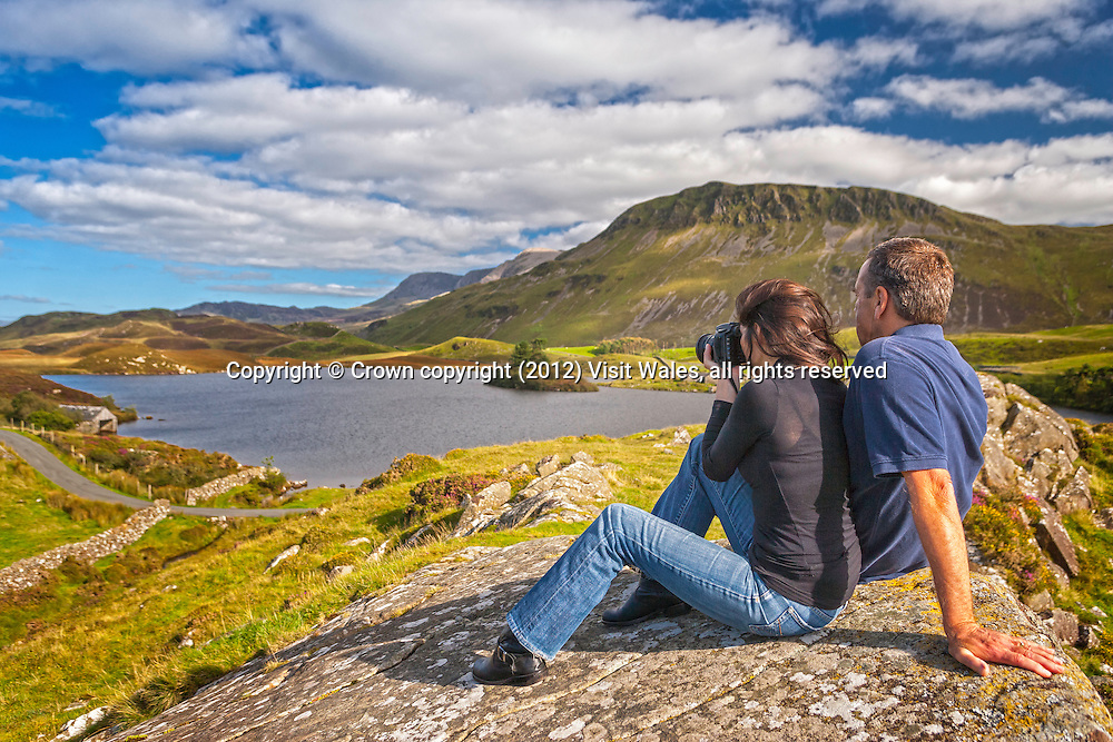 Couple resting with woman taking photograph, with lakes and Cadair Idris in background<br /> Llynnau Cregennen<br /> Snowdonia<br /> Gwynedd<br /> Mid<br /> Walking<br /> Activities and Sports
