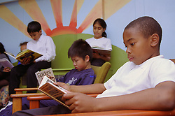Primary school children reading books in library,