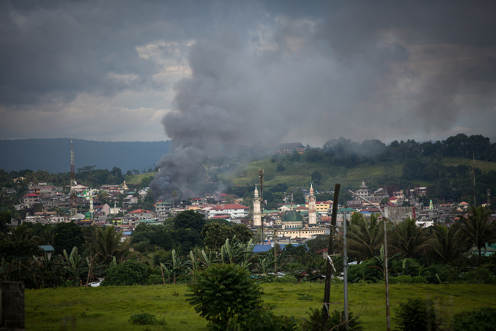 MARAWI, PHILIPPINES - JUNE 12: Black smoke comes from a burning building is seen after government troops' continuous assault with insurgents from the so-called Maute group, who has taken over large parts of the Marawi City, Philippines June 12, 2017. (Photo: Richard Atrero de Guzman/NUR Photo)