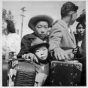 Turlock, Calif.--These young evacuees of Japanese ancestry are waiting their turn for baggage inspection upon arrival at this Assembly Center. -- Photographer: Lange, Dorothea -- Turlock, California. 5/2/42<br /> Contributing Institution:<br /> The Bancroft Library. University of California, Berkeley.