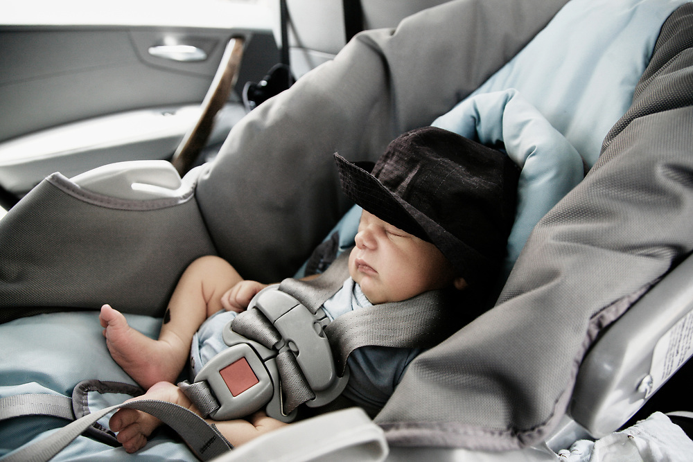 Baby properly fastened in car seat sleeping
