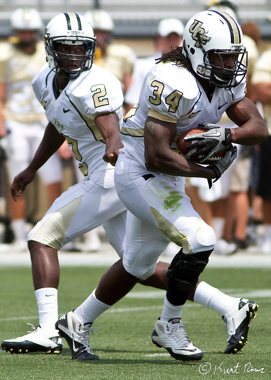 UCF quarterback Jeffrey Godfrey (2)gives the ball to UCF running back Brynn Harvey (34) during the Spring Football Game at Bright House Stadium, Orlando, FL on April 16, 2011.