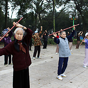Elderly women take part in an early morning keep fit class on the street in Hanoi, Vietnam.. For a county not know for it's sporting prowess, Hanoi, Vietnam's capital, appears to be gripped in a fitness frenzy. Before 6am street corners, parks and lake sides are a hive of activity as keep fit classes, Tai chi and personal exercise regimes are seen in abundance around the city. Particularly noticeable are Women's keep fit classes, often accompanied by loud poor quality western disco beat music as the occupants of the city get fit come rain or shine. Hanoi, Vietnam. 18th March 2012. Photo Tim Clayton