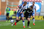 Wigan Athletic midfielder Michael Jacobs (17) and Brighton & Hove Albion midfielder Oliver Norwood (21) during the EFL Sky Bet Championship match between Wigan Athletic and Brighton and Hove Albion at the DW Stadium, Wigan, England on 22 October 2016.