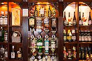 Rows of alcohol spirit bottles hanging in an English pub in London.  A pub is a drinking establishment and is a fundamental part to British culture and is often the focal point to a local community.   Many of these hard liquors are offering a special promotion to have a double measure of alcohol for a very small price, this type of promotion has been blamed for encouraging people to binge drink (heavy consumption of alcohol over a short period of time) and is a serious public health issue in the United Kingdom. Binge drinking is associated with a profound social harm, economic costs as well as increased disease burden.