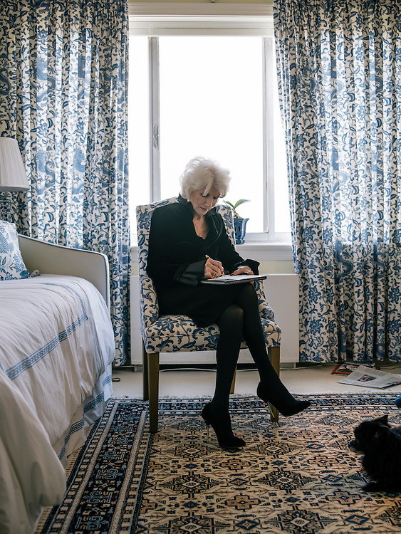 Diane Rehm writes a letter at her home while her dog, Maxie, watches on the 14th floor of a condominium complex in the Glover Park area of Washington, D.C.