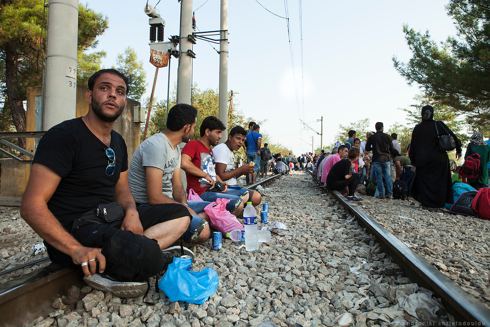 Refugees waiting on the train tracks near the border, for their turn to cross. Busses come regularly to pick them up after they cross. <br /> Refugees arrive at Eidomeni border by bus and some times on foot. There they can cross to the republic of Macedonia on foot.