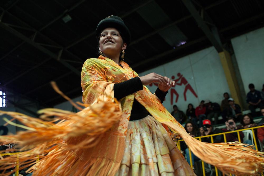 """Sarita """"La Romántica"""" baila al ritmo de la música moviendo su pollera en el momento de la entrada al cuadrilátero de lucha libre. Las Cholitas usan el vestido tradicional de los Aymara para luchar en el cuadrilátero, en El Alto, Bolivia, el 26 de Febrero de 2012."""