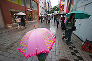 Myeong-dong shopping district. Shoppers in the rain.