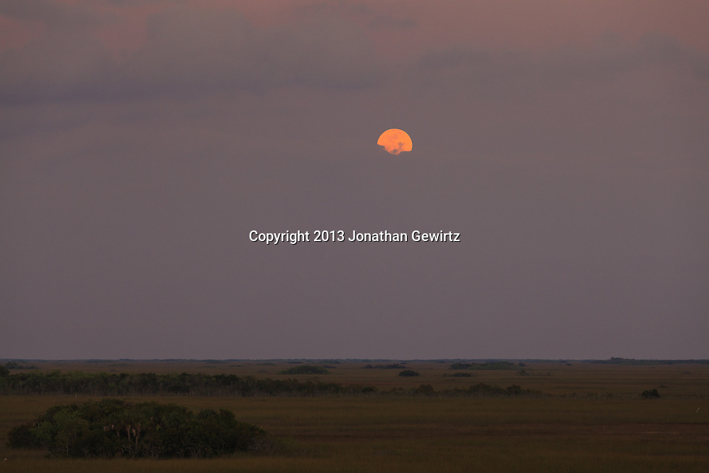 A full moon rises above low clouds over sawgrass prairie in the Shark Valley section of Everglades National Park, Florida. WATERMARKS WILL NOT APPEAR ON PRINTS OR LICENSED IMAGES.