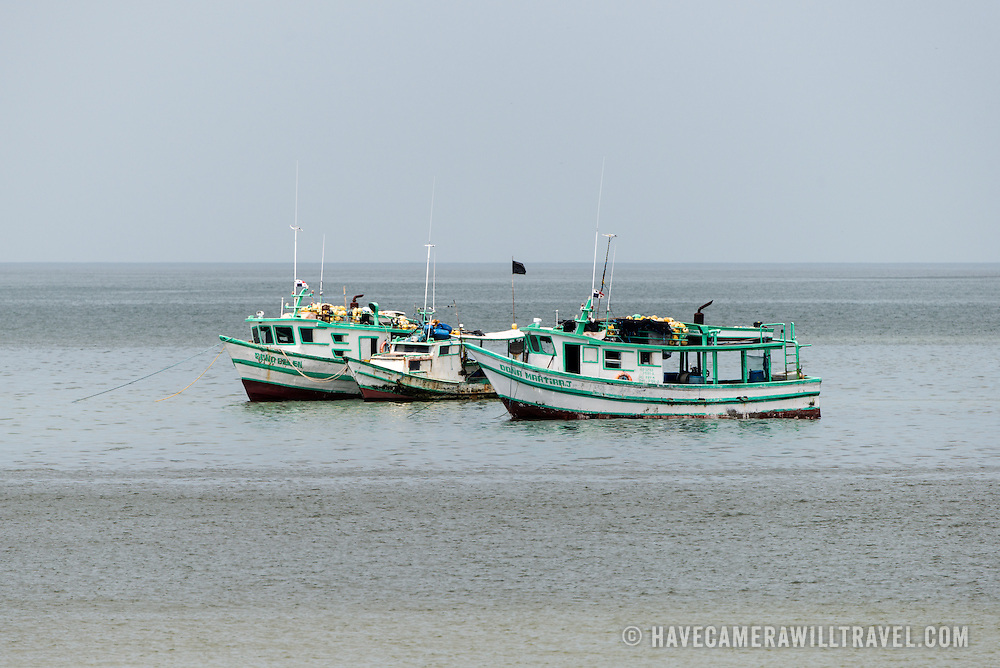 Three wooden fishing boats on the waterfront of Panama City, Panama, on Panama Bay.