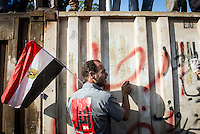 Protester bangs on a barricade near the presidential palace in Cairo.