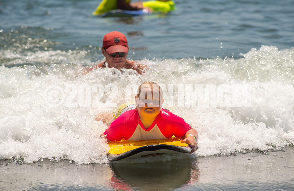 Lifeguard Ryan Comas, 20, of Philadelphia pushes Sage Praweckyj, 8, on her paddle board during the 11th annual 21 Down Beach Day Monday, July 15, 2019 at Schellenger Street beach in Wildwood, New Jersey. Every summer, the Wildwood Beach Patrol opens Lincoln Ave Beach for kids with down syndrome and their families for 21 Down Beach Day. Often, kids with down syndrome aren't comfortable in the ocean. Their parents can't just relax and watch them frolic. But on July 15th, the kids swim with seasoned Wildwood lifeguards on soft-top paddle boards. (Photo by William Thomas Cain / CAIN IMAGES)