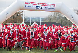 © Licensed to London News Pictures. 03/12/2017. Chew Magna, North Somerset, UK. (Runners agreed to be photographed for press and publicity) Over 500 Santas of all ages and fitness levels take part in the very first Chew Valley Santa Scramble. This Winter community event began with the children's 1k Mini Santa Scramble starting off the morning's action, in the grounds of Chew Valley School. Then 325 children over 11years and adults ran, walked or skipped around a 5k route from Chew Valley School, taking in the beautiful countryside of Chew Stoke and Chew Magna. Everyone wears a Santa Suit, included in the entry fee. Both events were officially started by Bristol's inspiring adventurer, Jim Plunkett-Cole – also known as Jim 'Gump' who, having completed his Jim Gump Challenge of running across America, educating and inspiring children to get active along the way, is now doing the same amongst local schools in the area, to encourage children to enjoy an active and healthy lifestyle. The event was organised by Chew Valley School's BTEC students in Sports Management and the Chew Valley 10k team. All funds raised will be divided between Chew Valley School, who are fundraising to provide two undercover tennis courts and Mend The Gap (www.mendthegap.org.uk), a local charity based in Langford, which the school is linked to. Photo credit: Simon Chapman/LNP
