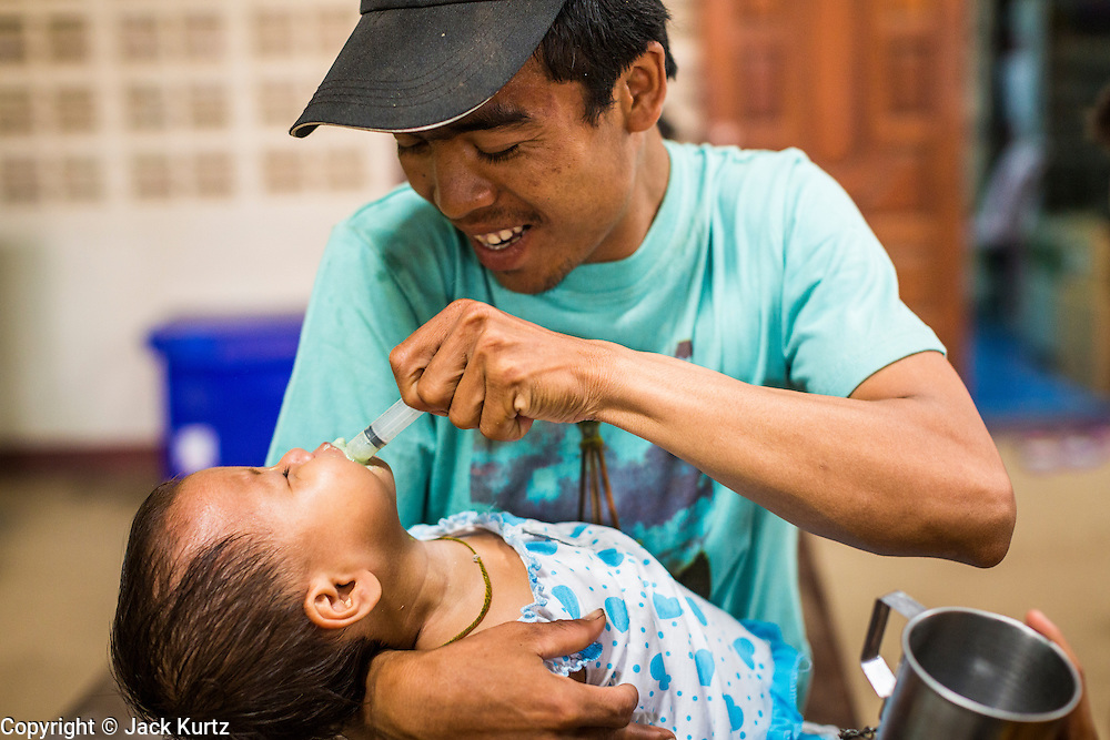 20 MAY 2013 - MAE KASA, TAK, THAILAND: A Burmese man tries to medicate his son at the SMRU clinic in Mae Kasa, Thailand. Health professionals are seeing increasing evidence of malaria resistant to artemisinin coming out of the jungles of Southeast Asia. Artemisinin has been the first choice for battling malaria in Southeast Asia for 20 years. In recent years though,  health care workers in Cambodia and Myanmar (Burma) are seeing signs that the malaria parasite is becoming resistant to artemisinin. Scientists who study malaria are concerned that history could repeat itself because chloroquine, an effective malaria treatment until the 1990s, first lost its effectiveness in Cambodia and Burma before spreading to Africa, which led to a spike in deaths there. Doctors at the Shaklo Malaria Research Unit (SMRU), which studies malaria along the Thai Burma border, are worried that artemisinin resistance is growing at a rapid pace. Dr. Aung Pyae Phyo, a Burmese physician at a SMRU clinic just a few meters from the Burmese border, said that in 2009, 90 percent of patients were cured with artemisinin, but in 2010, it dropped to about 70 percent and is now between 55 and 60 percent. He said the concern is that as it becomes more difficult to clear the parasite from a patient, progress that has been made in combating malaria will be lost and the disease could make a comeback in Southeast Asia.    PHOTO BY JACK KURTZ
