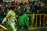"""Maria Eugenia Mamani Herrera, alias """"Claudina The Cursed"""", faces her opponent while the audience has fun taking photos of wrestling match. The Cholitas wear the traditional costumes of Aymara people during wrestling shows, in El Alto, Bolivia, February 19, 2012."""