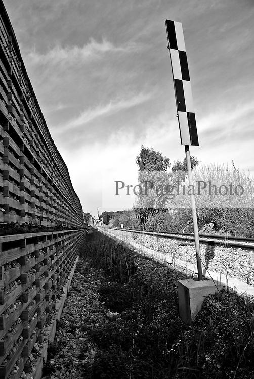 segnaletica ferroviaria lungo una tratta delle ferrovie del Salento, sulla sinistra si nota una barriera anti rumore costituita da gabbie di legno contenenti una grande quantità di pietre. Reportage che racconta le situazioni che si incontrano durante il viaggio lungo le linee ferroviarie SUD EST nel Salento.