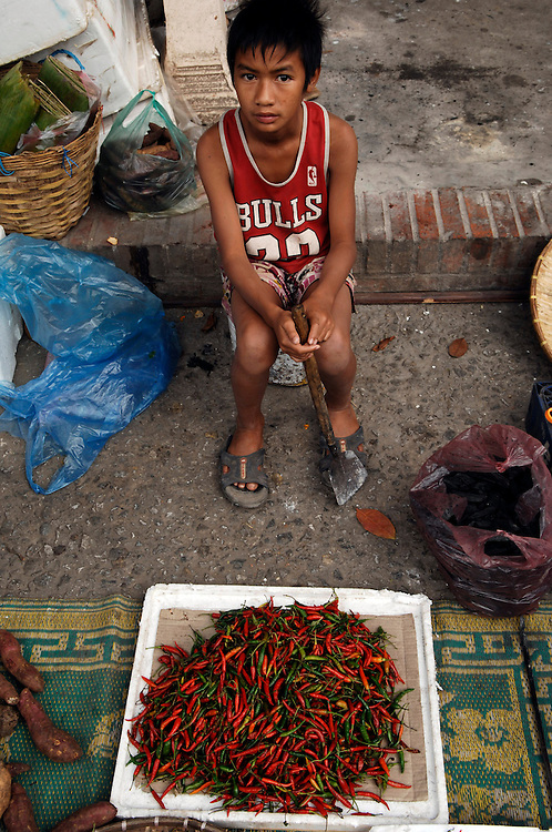 A boy wearing a Chicago Bulls vest selling chillis at the daily morning market of Luang Prabang.Vendors sell all kinds of fresh produce, from bread and eggs to river fish, flowers and a huge array of fruit and vegetables.