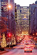 Park Avenue in Manhattan, view at dusk in winter with traffic and Christmas holiday lights on trees and the MetLife Building in the background, New York City.