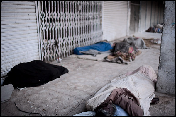 """Homeless people sleep on the ground. Among them there is a dead body of an heroin abuser. A few days later will be removed by the authorities. Rawalpindi, Pakistan, on thursday, November 27 2008.....""""Pakistan is one of the countries hardest hits by the narcotics abuse into the world, during the last years it is facing a dramatic crisis as it regards the heroin consumption. The Unodc (United Nations Office on Drugs and Crime) has reported a conspicuous decline in heroin production in Southeast Asia, while damage to a big expansion in Southwest Asia. Pakistan falls under the Golden Crescent, which is one of the two major illicit opium producing centres in Asia, situated in the mountain area at the borderline between Iran, Afghanistan and Pakistan itself. .During the last 20 years drug trafficking is flourishing in the Country. It is the key transit point for Afghan drugs, including heroin, opium, morphine, and hashish, bound for Western countries, the Arab states of the Persian Gulf and Africa..Hashish and heroin seem to be the preferred drugs prevalence among males in the age bracket of 15-45 years, women comprise only 3%. More then 5% of whole country's population (constituted by around 170 milion individuals),  are regular heroin users, this abuse is conspicuous as more of an urban phenomenon. The substance is usually smoked or the smoke is inhaled, while small number of injection cases have begun to emerge in some few areas..Statistics say, drug addicts have six years of education. Heroin has been identified as the drug predominantly responsible for creating unrest in the society."""""""