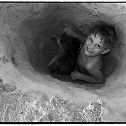 A young boy in a whole he has just dug on the beach.