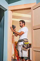 A construction worker doing finish work on a door frame inside a home.