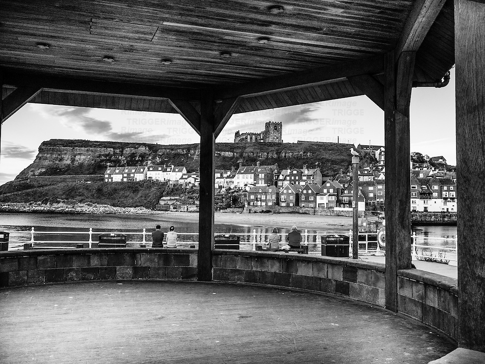 People sitting on the quayside at Whitby harbour