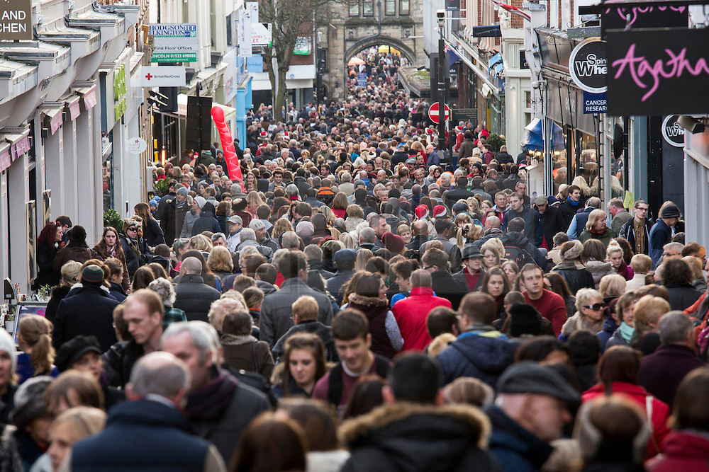 """© Licensed to London News Pictures. 7/12/2013. Lincoln, UK. Lincoln City Centre was packed with Christmas shoppers this weekend. Pictured, tightly packed shoppers struggle to make their way up the High Street in Lincoln. Thousands of shoppers filled the City Centre and stewards were called in to direct people up the narrow """"Steep Hill"""" towards the upper area of Lincoln near the Cathedral. Photo credit : Dave Warren/LNP"""