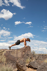 shirtless athletic man doing pushups on a rock formation